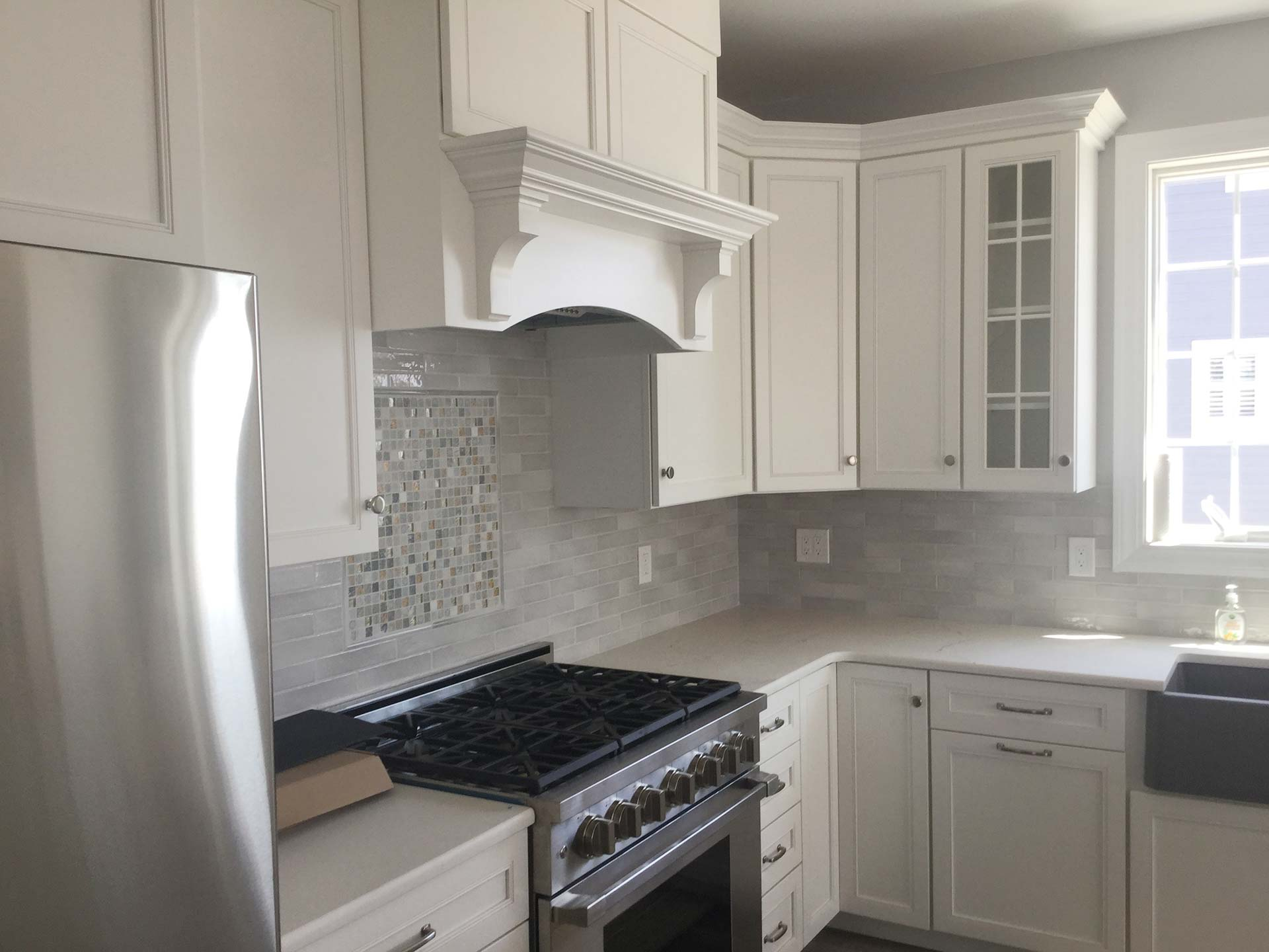 White kitchen cabinets and custom vent hood